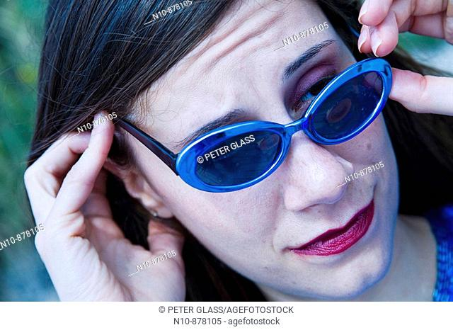 Young woman adjusting her sunglasses