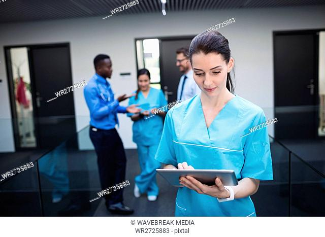 Nurse using digital tablet in hospital corridor