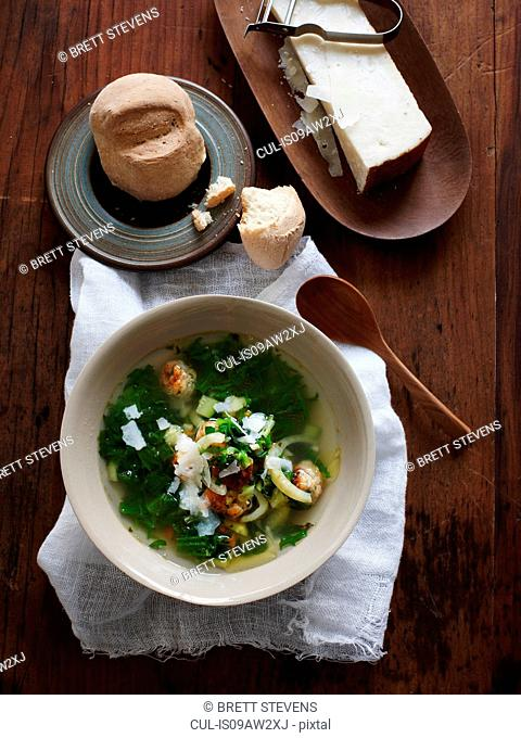 Overhead view of italian wedding soup with bread roll and parmesan cheese