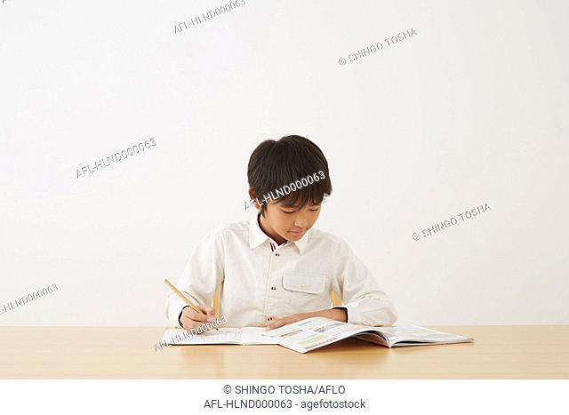 Young boy doing his homework on wooden desk