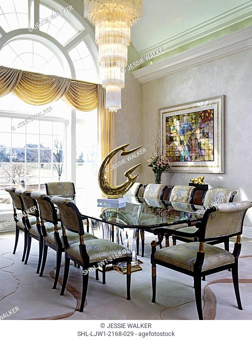 DINING ROOM: Modern, tiered chandelier, glass table, modern sculpture on table, formal swag drapes over large 1 1/2 story window, Palladian, vaulted ceiling