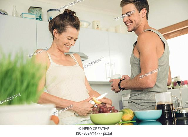 Young couple laughing whilst preparing breakfast at kitchen counter