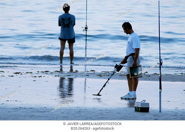 Fisherman and man using a metal detector at beach. Hendaye. France