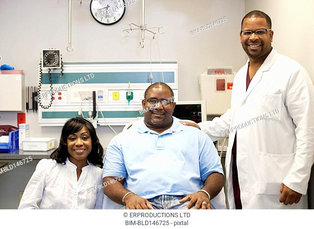 Doctor standing in hospital with patient and patient's wife