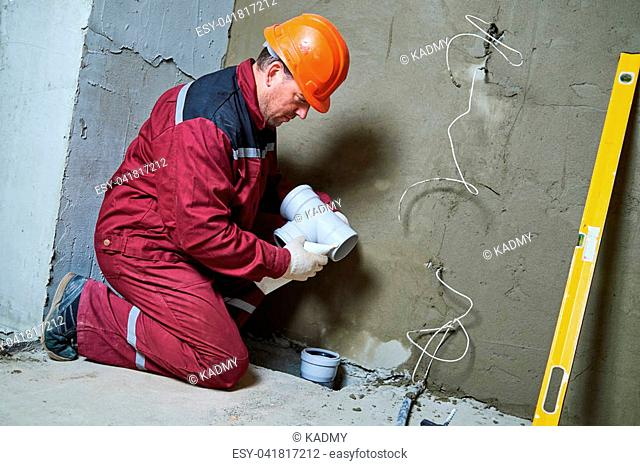 sewerage system. Plumber worker installing plastic sewage pipe fitting at construction site