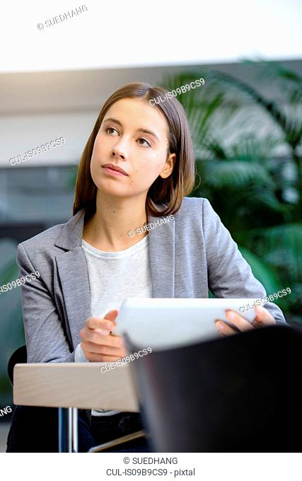 Young businesswoman with laptop in contemplation at office desk