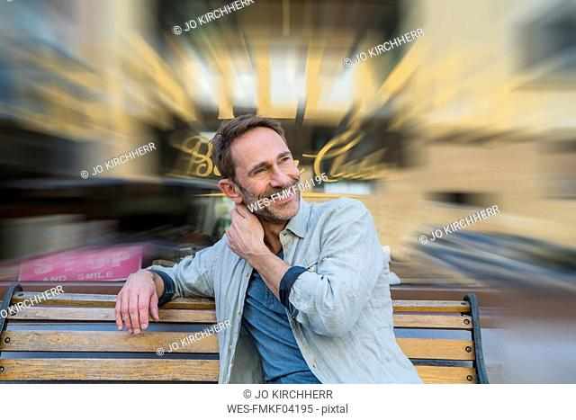 Portrait of smiling mature man sitting on wooden bench