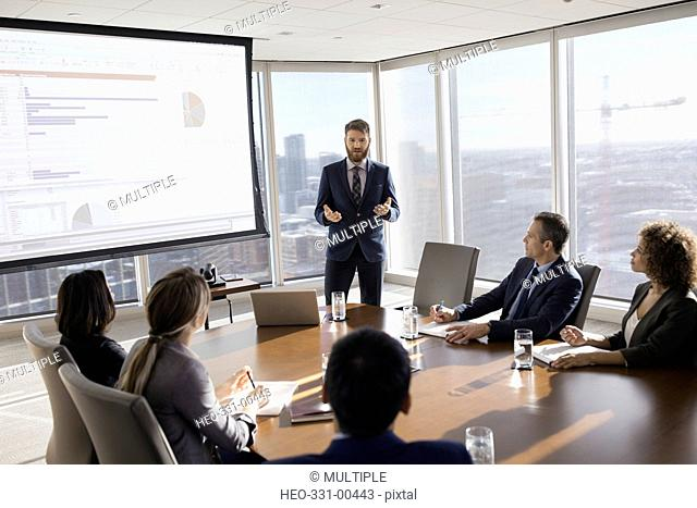 Businessman leading presentation at projection screen in conference room meeting