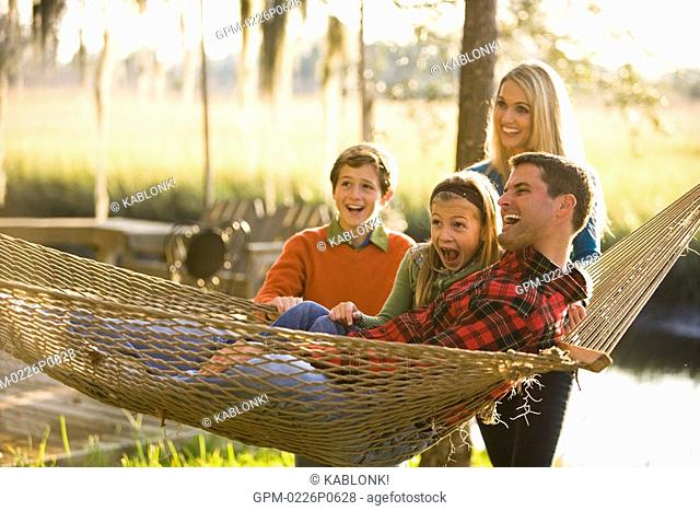 Portrait of young happy family hanging out around hammock, looking at camera