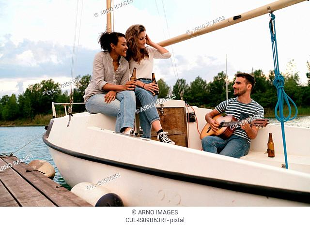 Three friends relaxing on moored sailing boat, drinking beer, man playing guitar