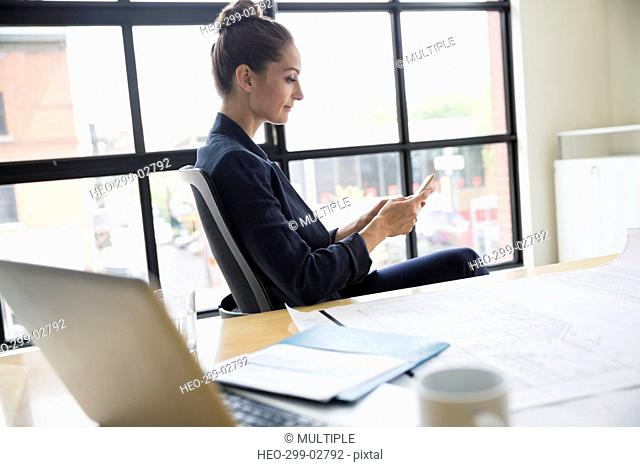 Female architect texting with cell phone in conference room