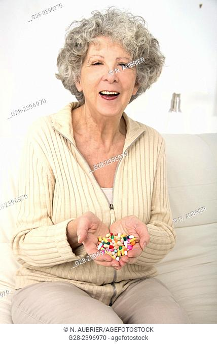 Beautiful surprised senior woman holding colorful tablets in her hands and laughing