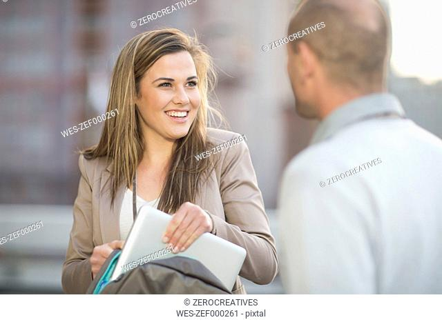 Portrait of smiling businesswoman communicating with a colleague