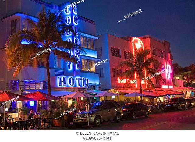 Art deco hotels at night with neon lights along Ocean Drive, in the Art Deco District of South Beach, Miami, Florida  People are eating at the sidewalk...
