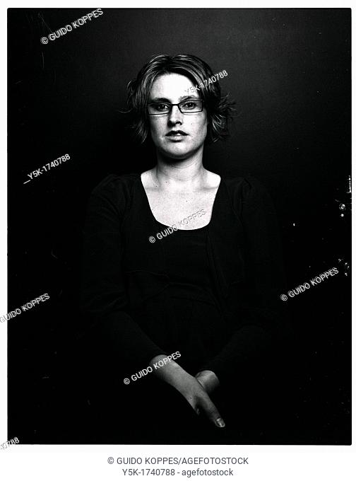 Rotterdam, Netherlands. Analog black and white portrait of a young adult woman, wearing glasses due to poor eyesight. Image produced using a 6 X 7 black and...