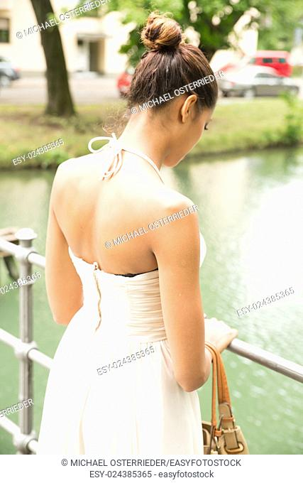 A young girl standing on a bridge