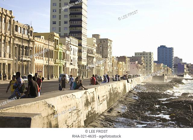 View along The Malecon showing people sitting on the seawall enjoying the evening sunshine, Havana, Cuba, West Indies, Central America