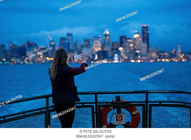 Caucasian woman on boat photographing urban waterfront with cell phone
