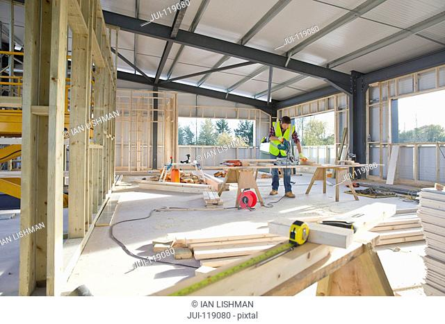 Carpenter wearing hi viz cutting wood with circular power saw in building construction site interior