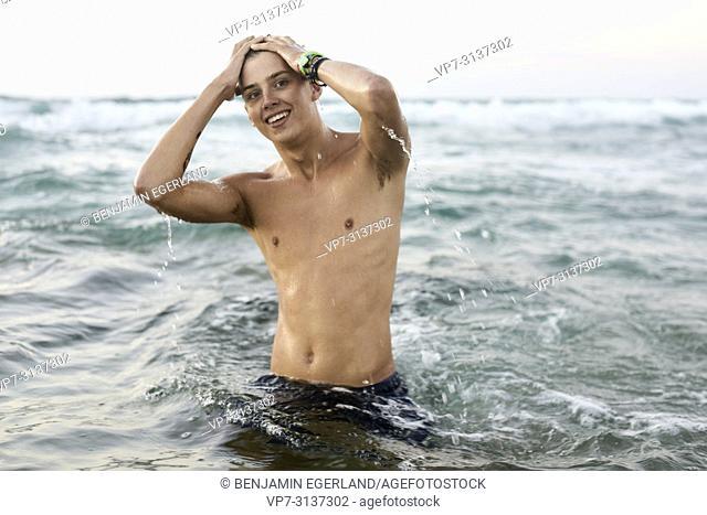 Young man in sea water, Potamos beach, in holiday destination Malia, Crete, Greece