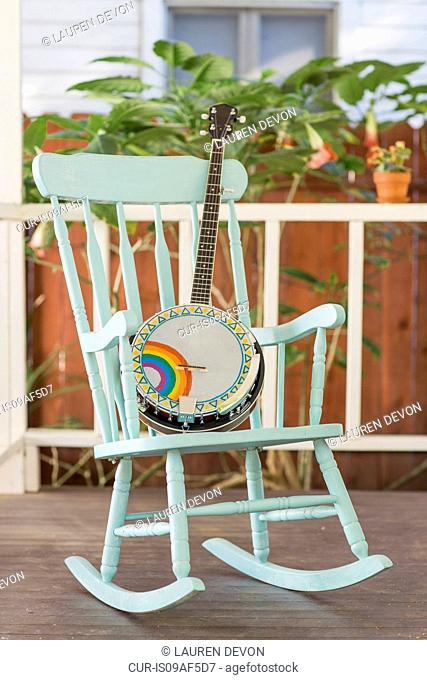 Banjo and rocking chair on outside porch