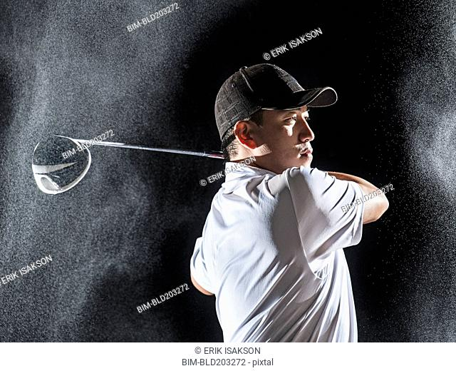 Asian golf player swinging club in rain