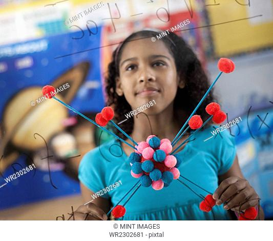 A girl holding a molecular structure and looking at a board of equations and formulae in the classroom