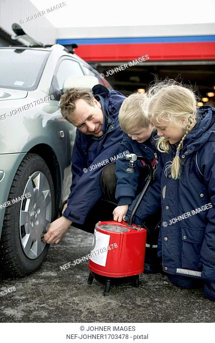 Man checking air pressure in tire with children