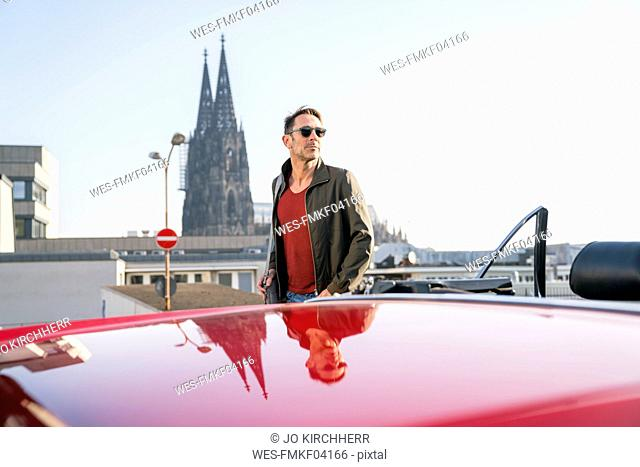 Germany, Cologne, portrait of mature man leaning with his parked sports car