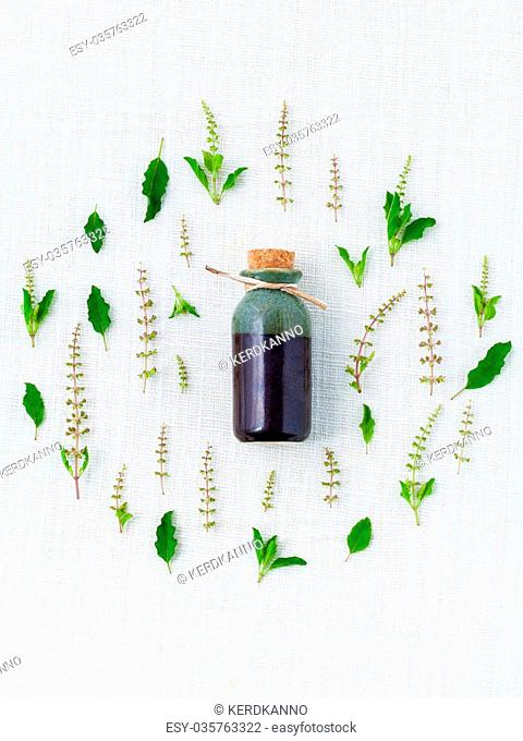 Bottle of essential oil, with holy basil leaf and flower