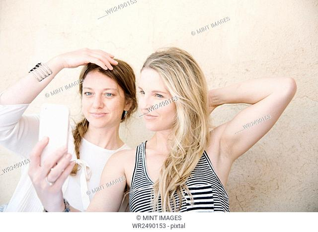 Two smiling women taking a selfie with a cell phone