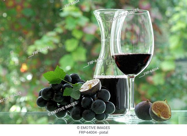 Red wine in a carafe, wine glass and red wine grapes