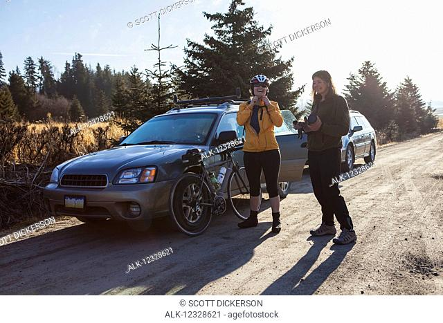 Two women preparing for a bike ride near Homer, Kenai Peninsula, South-central Alaska; Alaska, United States of America