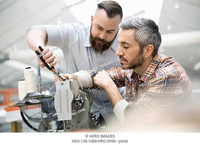 Workers using sewing machine in textile manufacturing plant