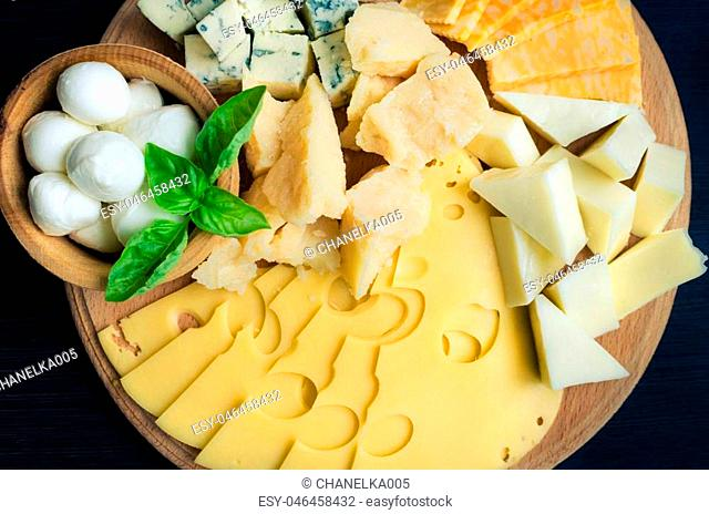 Cheese plate: Parmesan, cheddar, gouda, mozzarella and other with basil on wooden board on dark background. Tasty appetizers. Top view