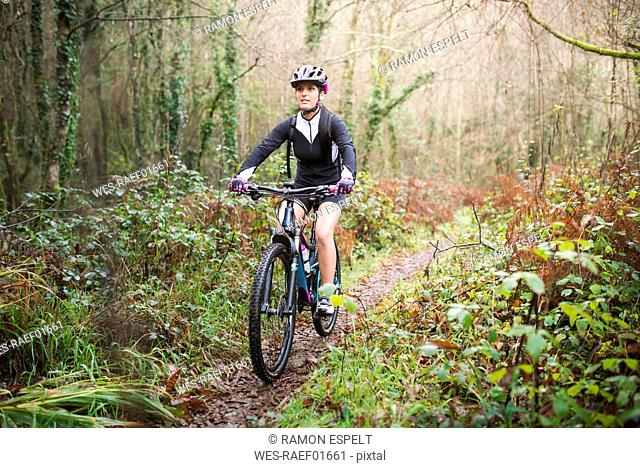 Female mountain biker riding her bike on a trail in forest
