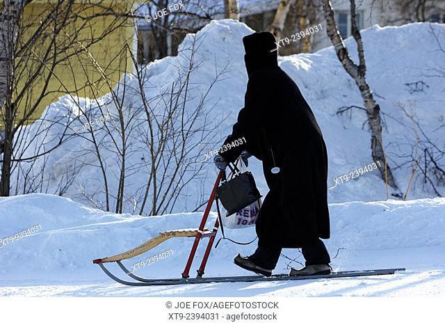 old woman carrying shopping home using a kicksled spark kirkenes finnmark norway europe
