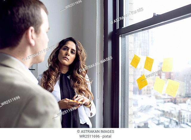 Businesswoman planning with male colleague using sticky notes by window