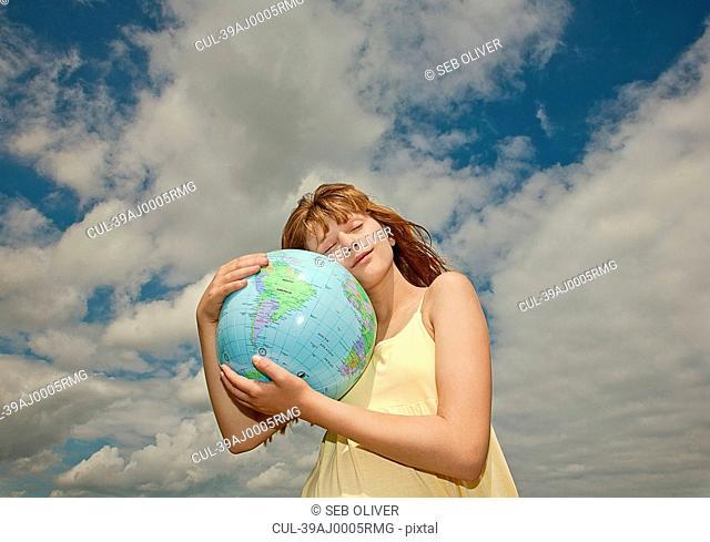 Girl hugging globe outdoors