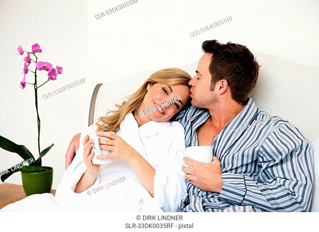 Couple in bathrobes drinking coffee