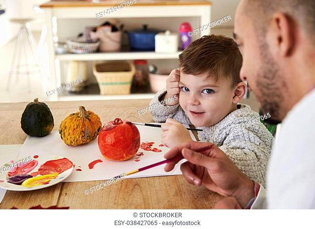 Father And Son Decorating Halloween Pumpkins At Home