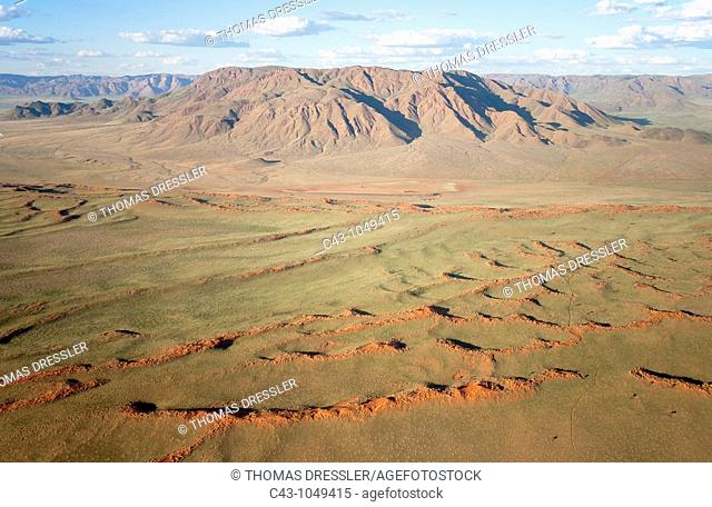 Namib - Aerial view of grass-grown sand dunes against the background of the Losberg at the edge of the Namib Desert  In March during the rainy season with a...