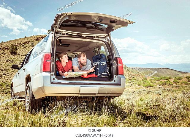 Mature man and teenage son pointing whilst reading map from off road vehicle, Bridger, Montana, USA