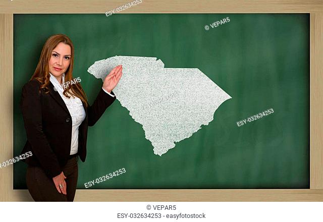Successful, beautiful and confident young woman showing map of south carolina on blackboard for presentation, marketing research and tourist advertising
