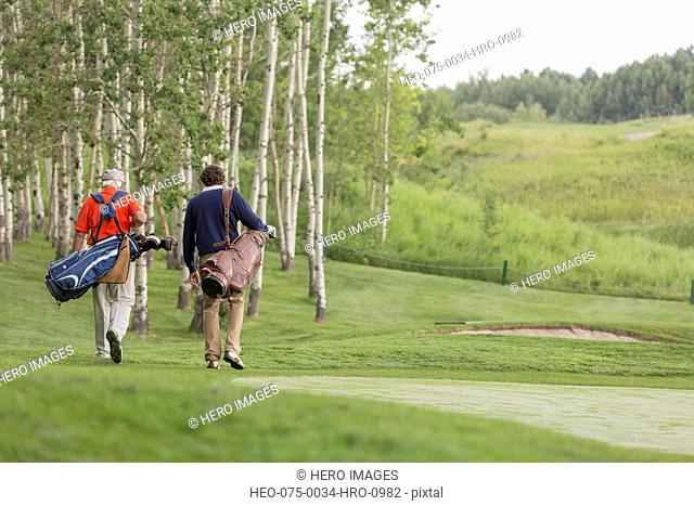 view from behind of golfers walking off tee