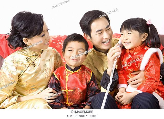 Young family in traditional clothes smiling happily, on the phone