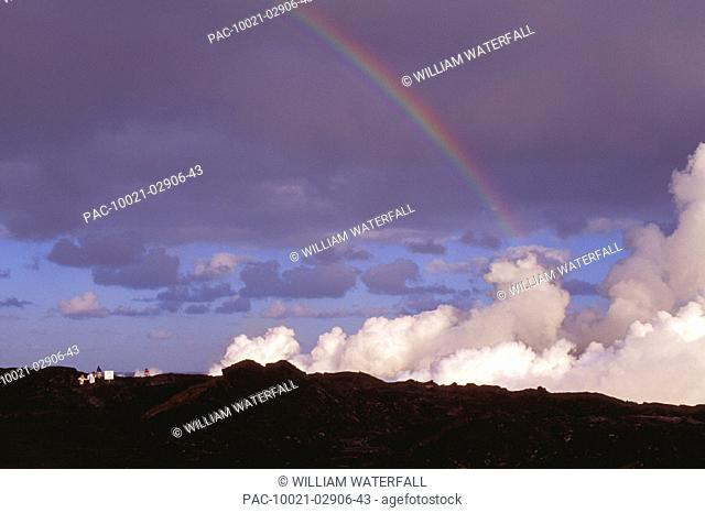 Hawaii, Big Island, Lava flows into ocean, steam rises, rainbow, blue skies
