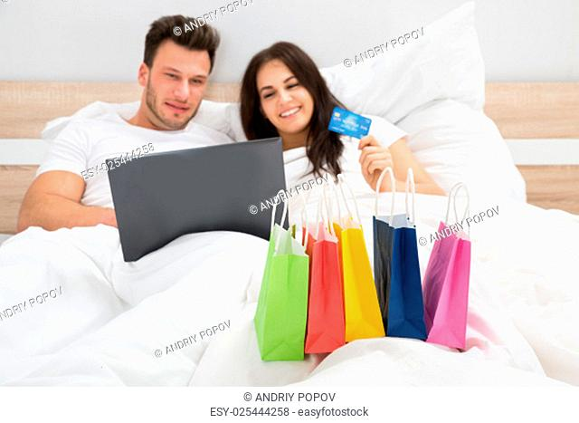 Colorful Shopping Bags In Front Of Couple Shopping Online With Credit Card On Bed