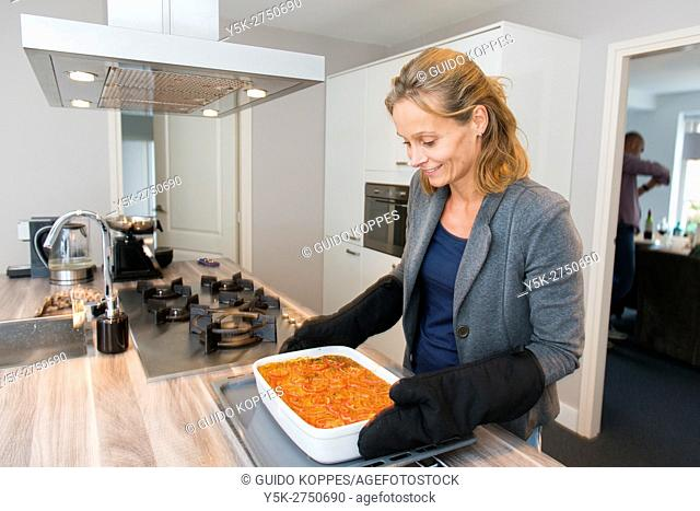 Kaatsheuvel, Netherlands. Mid adult woman enjoying her freshly made Lasagna dish dinner, just after romoving it from her kitchen oven and stove