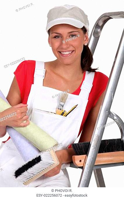 Female decorator with wallpaper
